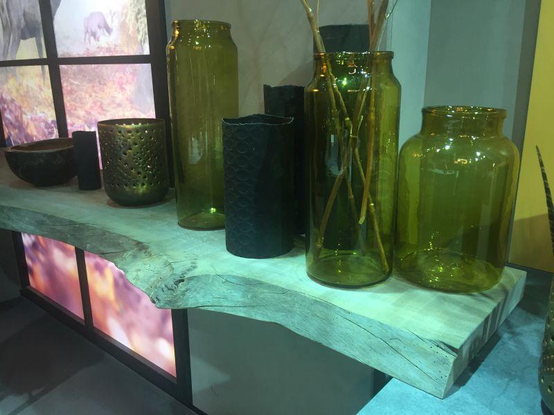 Green empty glass vases on a wood shelf