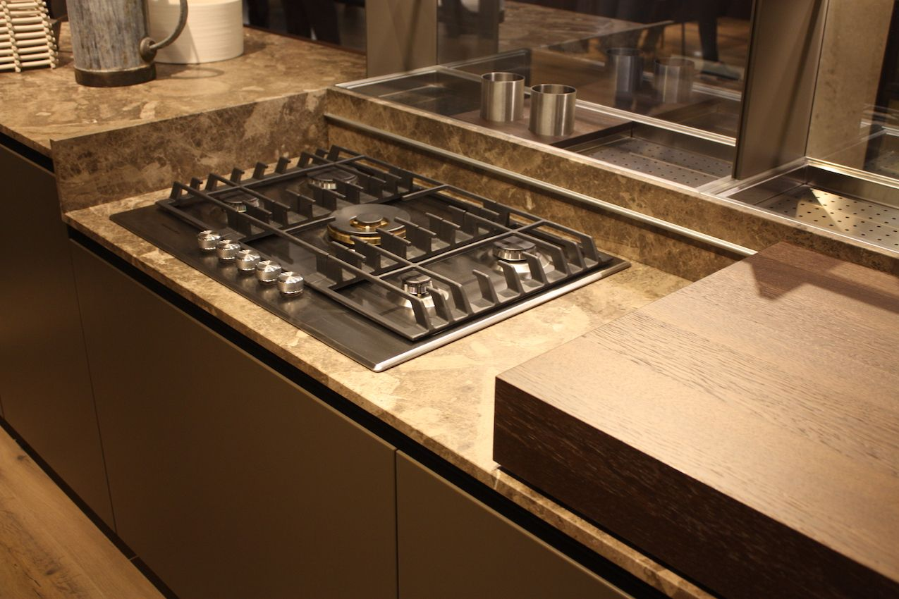 Even gas cooktops can be part of a hidden kitchen when a sliding cover is included. This is by Ernestomeda.