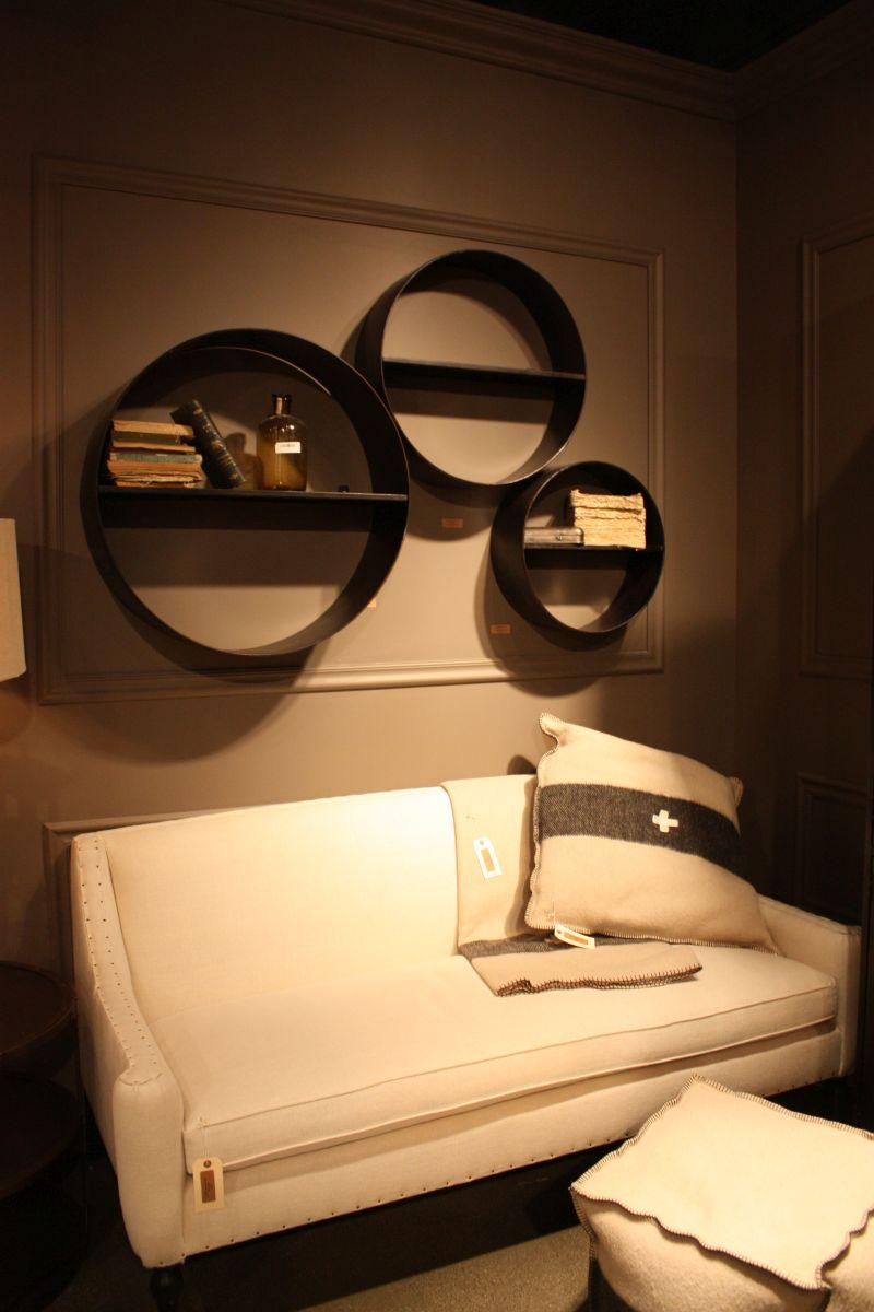Round metallic wall shelves above sofa