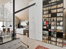 A tall bookcase doubles as a space divider, concealing a cozy nook behind its shelves