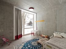 The concrete walls and ceiling are softened by textile rugs, curtains and other highlights