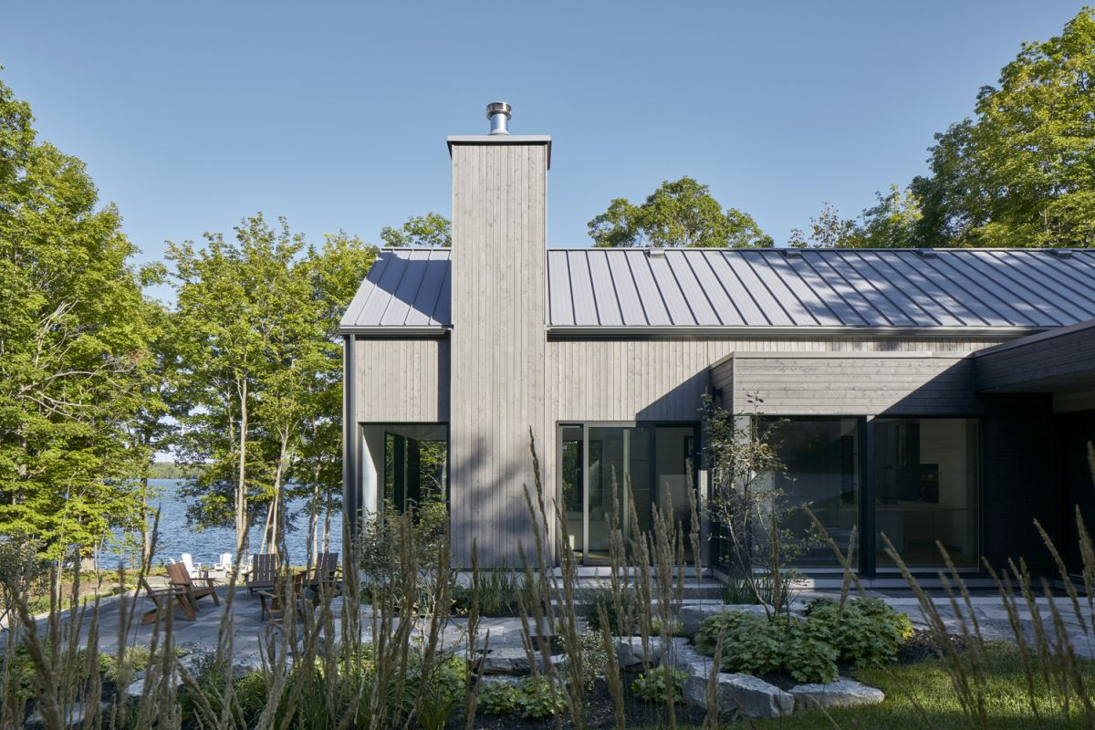 On the exterior the house features gray walls and zinc-colored metal roof panels