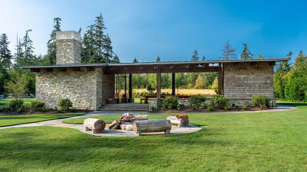 A fire pit is placed some distance away from the house, with log seating around it