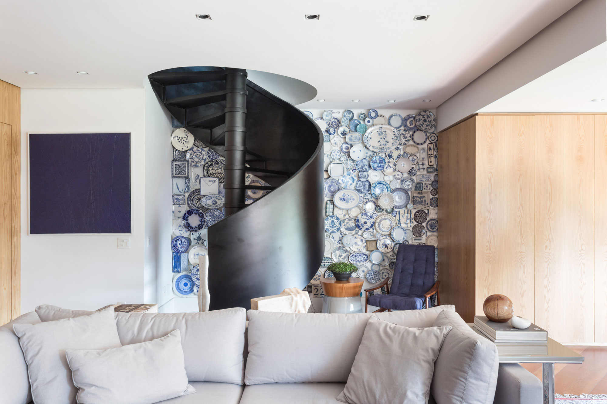 Apartment In Brazil With Blue Plates Accent Wall And Spiral Staircase