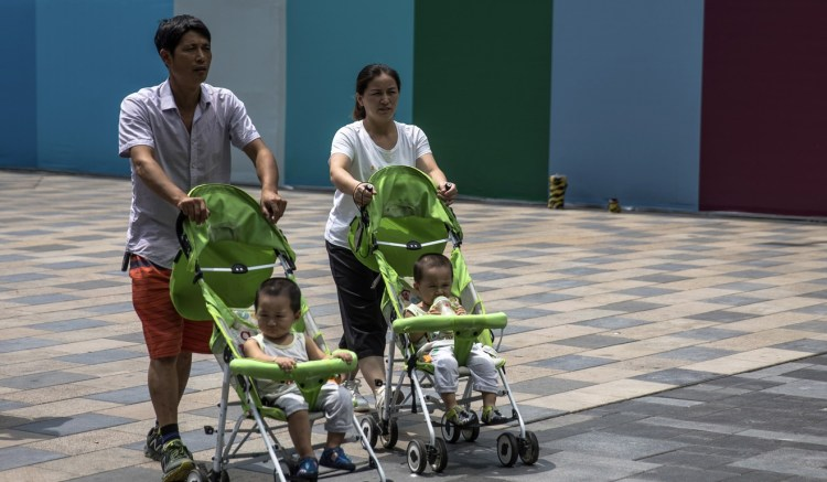 Parents with their children walk in the Sanlitun area of Beijing. Photo: EPA-EFE