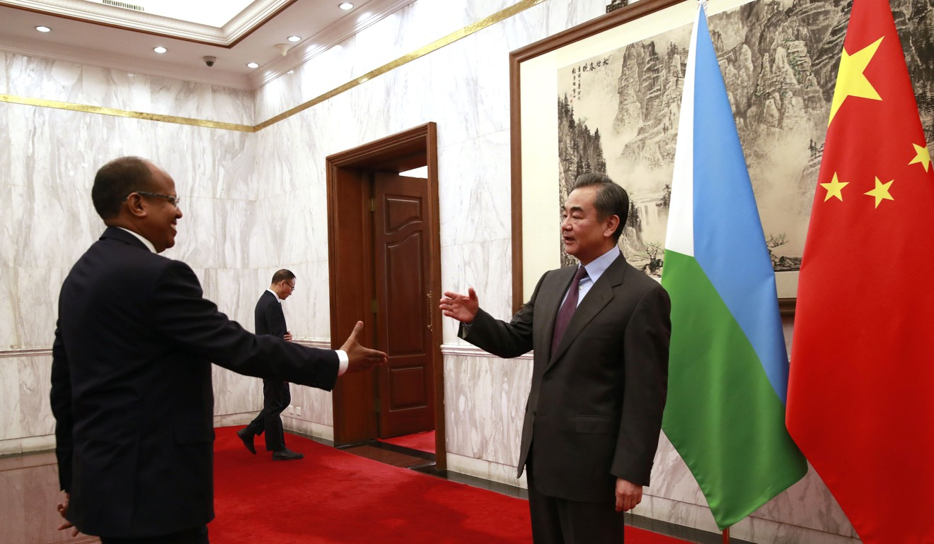 Djibouti Foreign Minister Mahamoud Ali Youssouf approaches his Chinese counterpart Wang Yi to shake hands during their meeting in Beijing earlier this year. Photo: AP