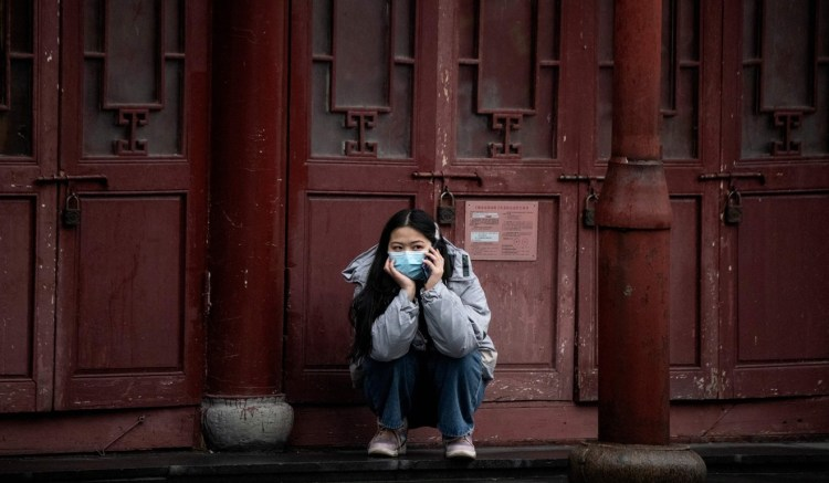 A woman wearing a protective face mask uses her mobile phone in Shanghai. Photo: AFP