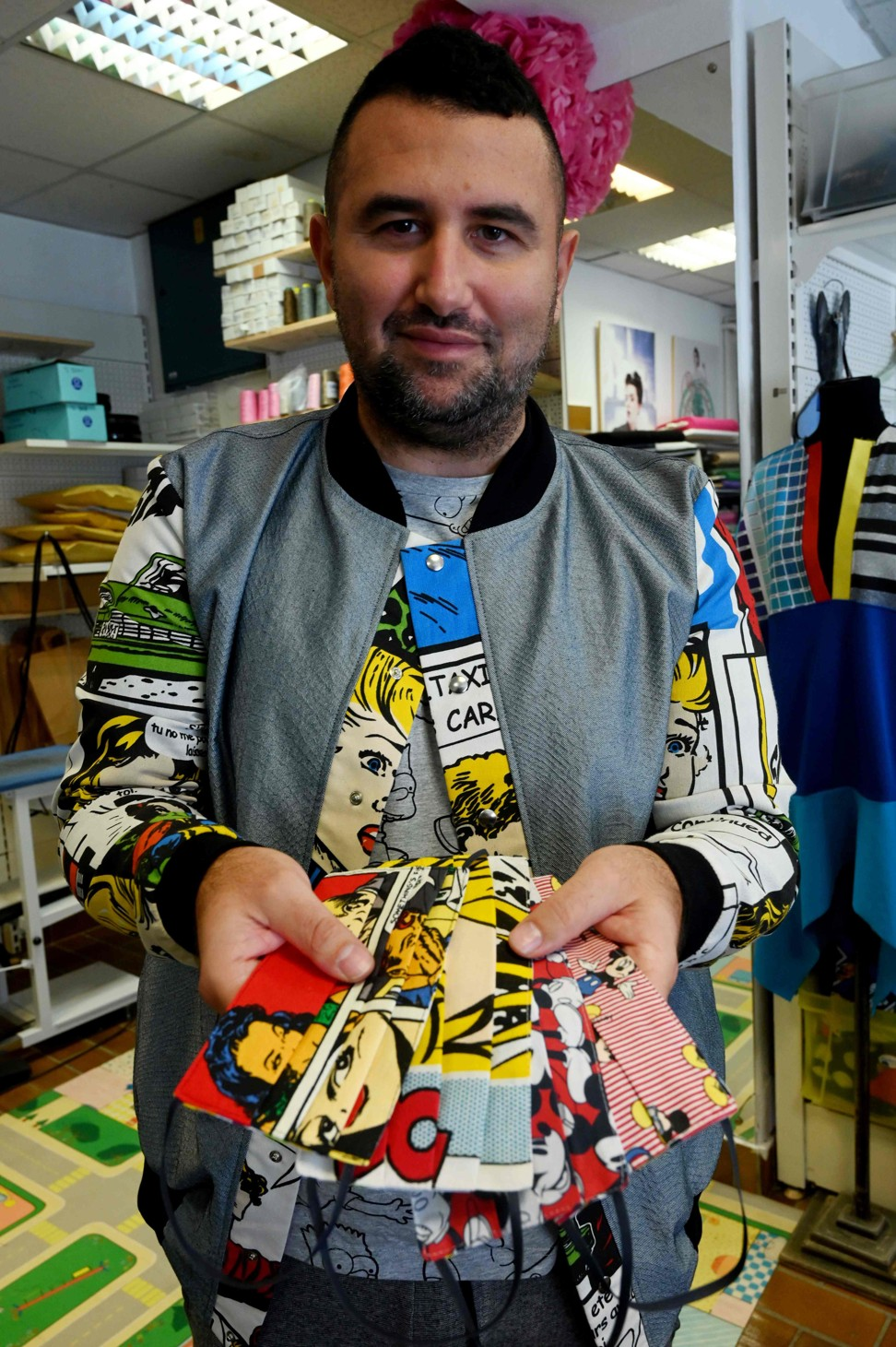 Croatian designer Aragovic shows a selection of face masks with his designs on them. Photo: AFP