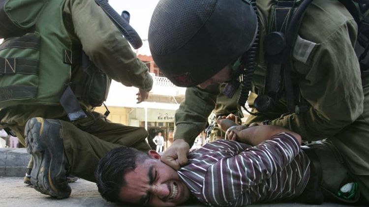 Israeli soldiers arrest a Palestinian youth following clashes that erupted during a demonstration to mark the fourth anniversary of late Palestinian leader Yasser Arafat's death in the West Bank city of Hebron on November 11, 2008