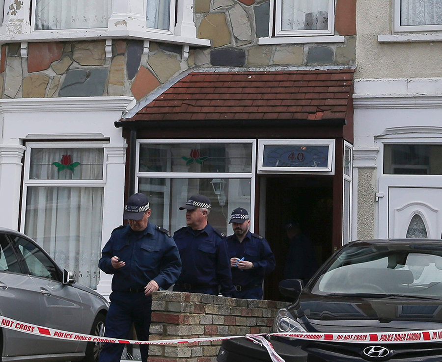 Police officers leave the property in Ilford