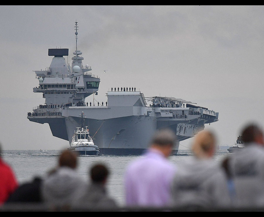 People line the shore to watch as tug boats manoeuvre the 65,000-tonne British aircraft carrier HMS Queen Elizabeth into Portsmouth Harbour