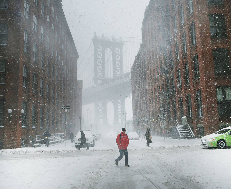 Pedestrians walk in the snow and wind in Brooklyn.