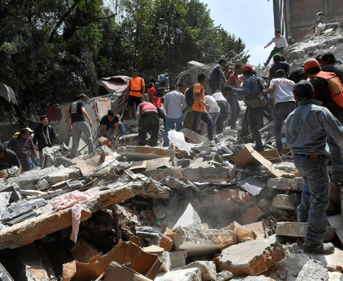 People remove debris of a building which