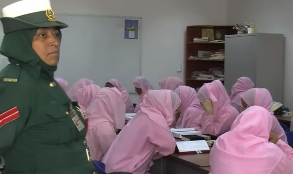 Women are seen reading books in Arabic in prison