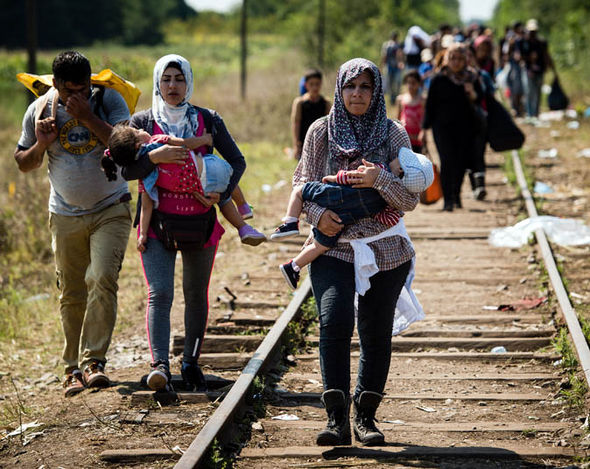 Migrants walking down the railway