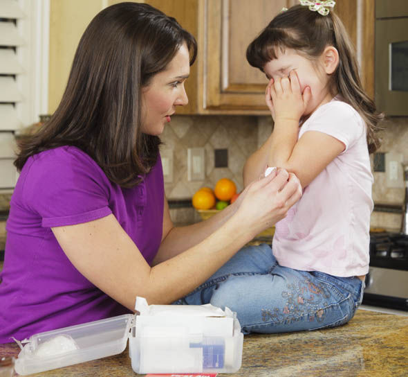 A mother uses first aid on a child