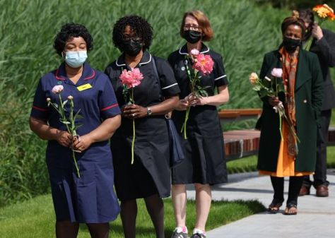 NHS staff queue to leave a rose in the garden