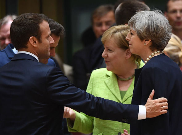 Macron reaches to touch Theresa May at the EU summit