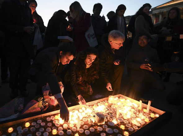 People lighting candles at Westminster