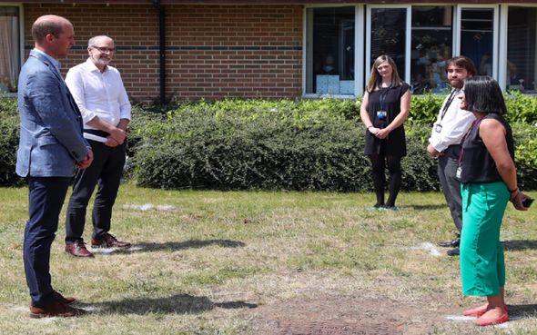 Prince William talks to investigators on a lawn.