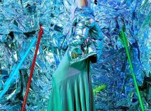 model in silver room wearing silver dress and coat