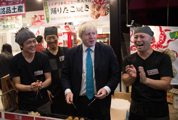 Boris Johnson helps cook octopus balls in the Dotonbori district of central Osaka