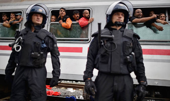 Police guard a train full of migrants in Croatia
