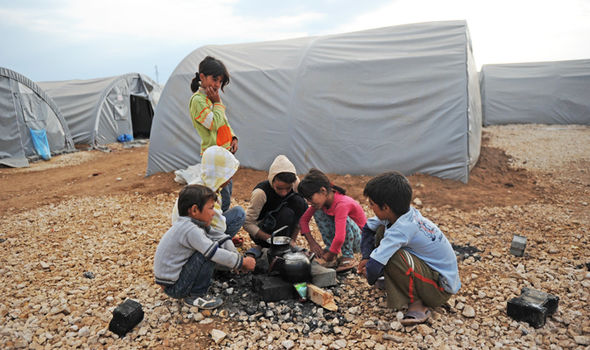 Kurdish children prepare tea in a refugee camp