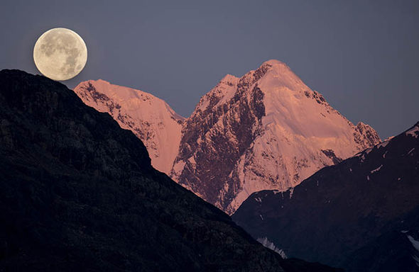 Pink moon rising over some mountains