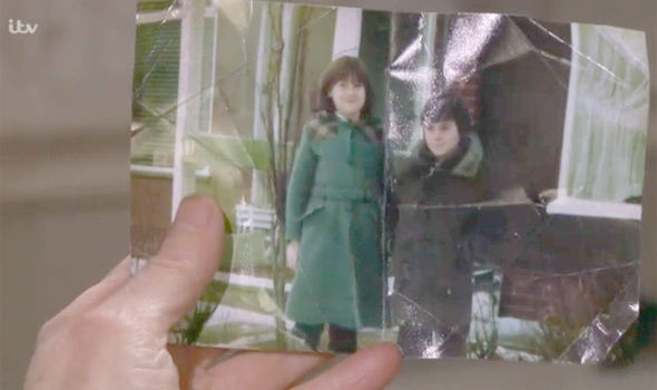 Faith Dingle looks at it a photo of Chas and Cain on Emmerdale