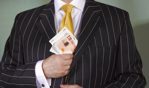 Suited man puts cash in jacket pocket