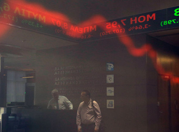 Employees of the Stock Exchange are reflected on a display showing stock price movements in Athens