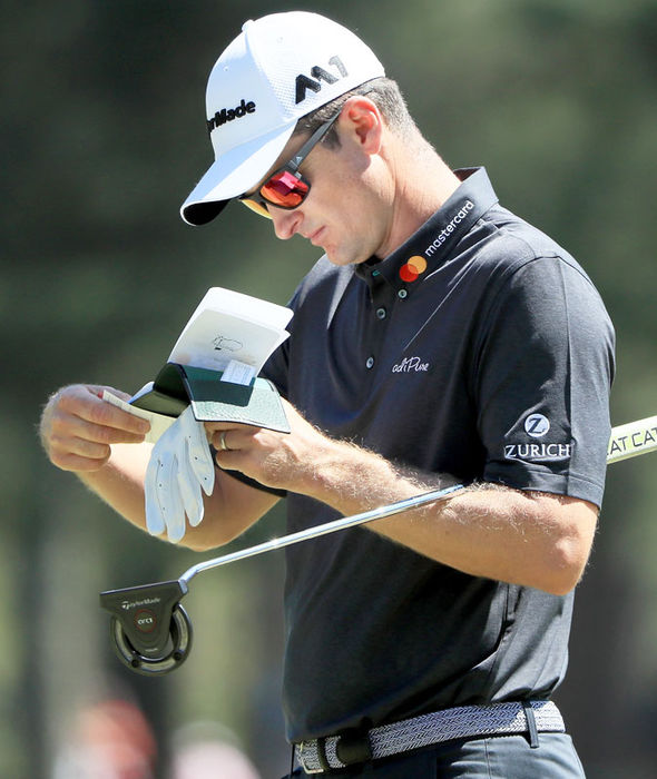 Justin Rose checks his scorecard at Augusta