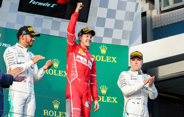 Mercedes drivers Valtteri Bottas and Lewis Hamilton celebrate with Ferrari's Sebastian Vettel