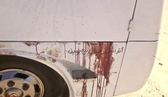 Blood stains the outside of a bus attacked by gunmen