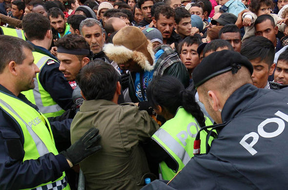 Police forces try to control the crowd as migrants wait to board busses