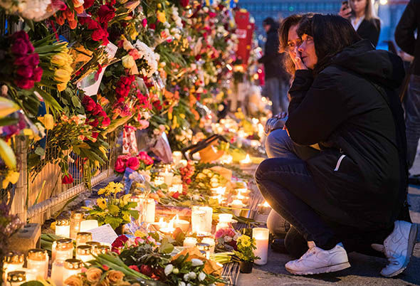 Mourners pay their respects to the victims in Stockholm