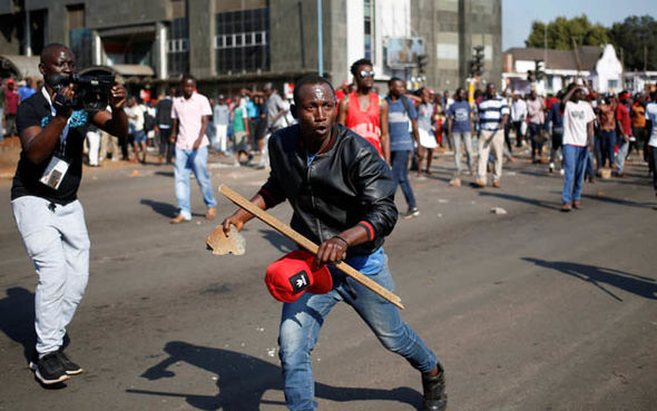 Protesters are seen armed with rocks and sticks