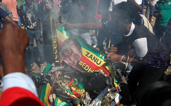 Protesters burning a Mnangagwa banner
