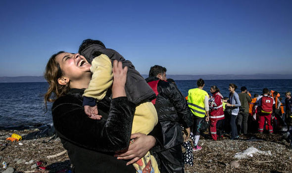 Mother holds her baby in relief ashore