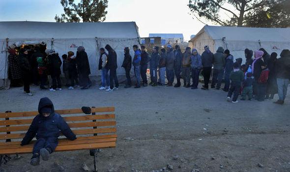 Los migrantes hacen cola en un campamento en Grecia