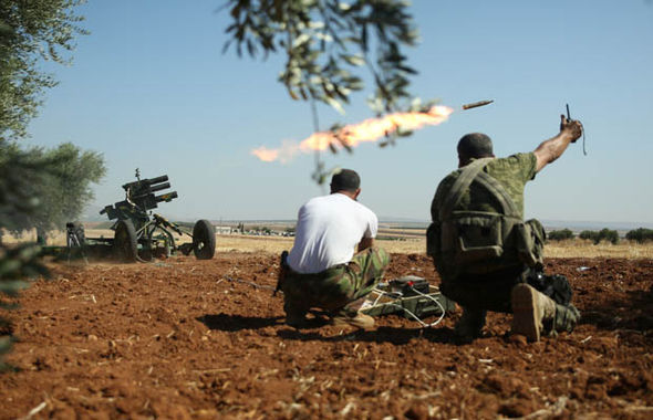 Syrian rebel forces fight against IS with shells