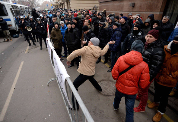 A protester throws a stone towards the Turkish embassy in Moscow