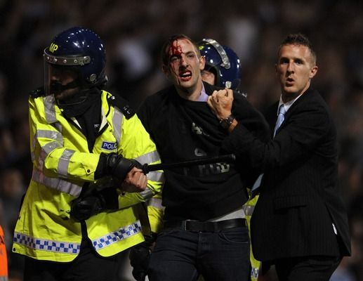 A bloodied fan is led off the pitch at Upton Park