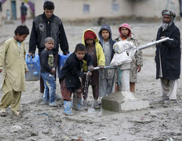 Children drink water from a public water pump on the outskirts of Kabul, Afghanistan
