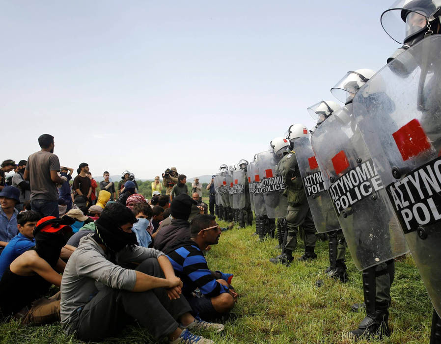 Protestors gesture towards Macedonia police as migrants and refugees hold a protest to call for the reopening of the border near their makeshift camp at the Greek-Macedonian border