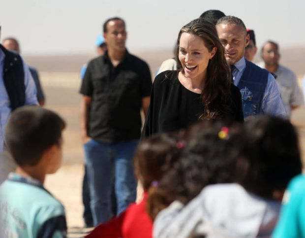 US actress and UNHCR special envoy and Goodwill Ambassador Angelina Jolie greets children during a press conference at Al- Azraq camp for Syrian refugees.