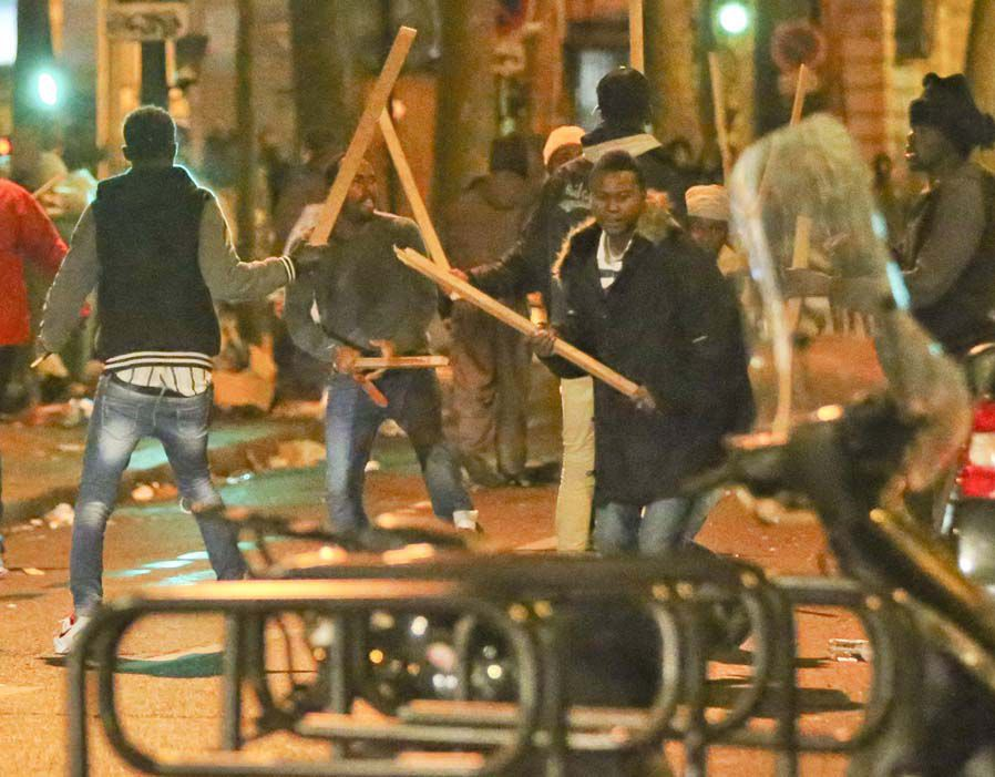 Migrants fightingwith wooden planks in Paris