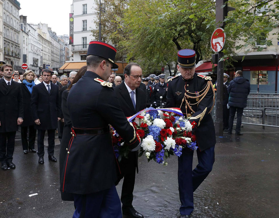 French President Francois Hollande and Paris Mayor Anne Hidalgo lay a wreath of flowers as they unveil a commemorative plaque next to the