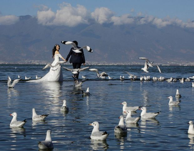A couple pose for a wedding photo at Erhai lake in Dali